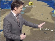 A presenter stands in front of the weather map