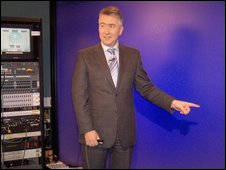 A presenter stands in front a blue screen