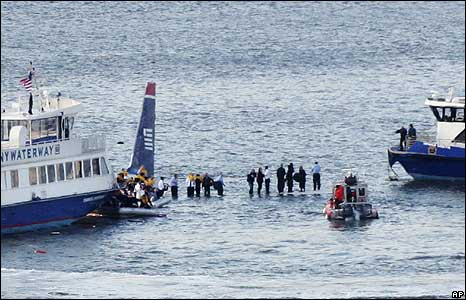 Passengers stand on the wings of the ditched plane