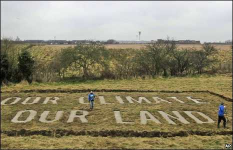 Greenpeace protestors rake a slogan created on a plot of land they've purchased in the village of Sipson beside Heathrow Airport in London