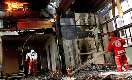 Medics examine the damage inside a burning building of the Quds hospital