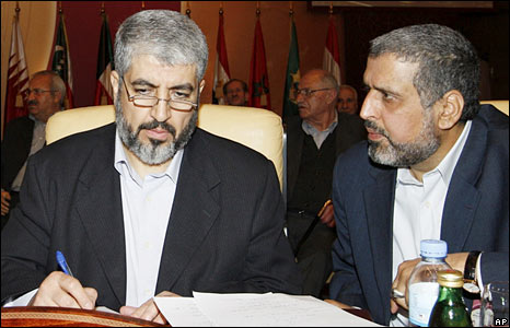 Syria-based Hamas leader Khaled Meshaal (left) and Islamic Jihad leader Ramadan Shallah talk during an emergency meeting of Arab leaders in Doha, Qatar
