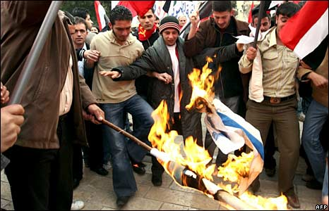 Syrian demonstrators burn an Israeli flag during a rally against Israel's offensive in Gaza