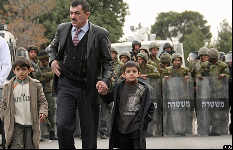 A Palestinian father and his children walk past Israeli anti-riot police in the Arab East Jerusalem
