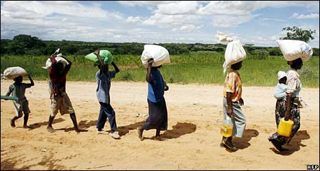 Zimbabweans carrying food aid