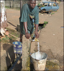 Freetown resident getting water from public tap