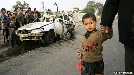 Palestinian children stand around a car damaged by an Israeli airstrike in Gaza (16/01/2009)