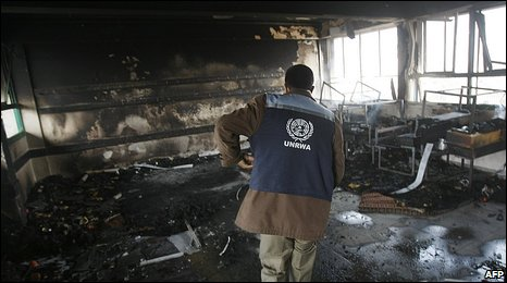 An UNRWA worker inspects a bombed building in Gaza