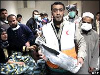 أحد أعضاء الطاقم الطبي يحمل بقايا القذيفة التي ضربت مستشفى القدس