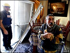 An Israeli man gestures as a fireman inspects the damage inside his house after a rocket attack in the southern Israeli town of Sderot on 15 January 2009