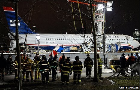 Firemen watch the plane being lifted from the Hudson River.