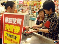 Taiwanese shopper hands vouchers to assistant