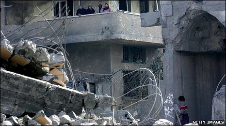 A group of people stand on a balcony by a destroyed mosque in Beit Lahiya