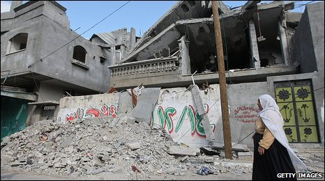 A Palestinian woman walks past a damaged building in Beit Lahiya