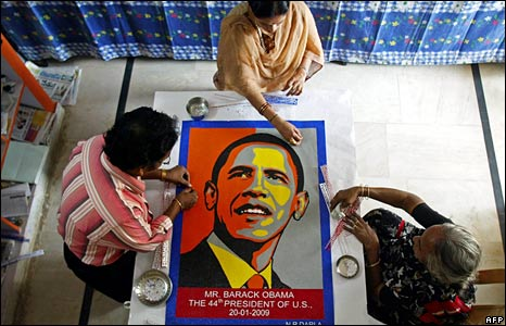 Indian artist Darla Nageswara Rao works on a portrait of Barack Obama with his wife Jyothi Kumari (centre) and his mother Savithri.