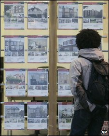 A man looks in estate agent's window