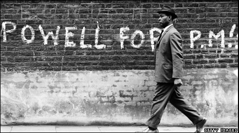A black man walks past grafitti supporting Eoch Powell in the 1960s