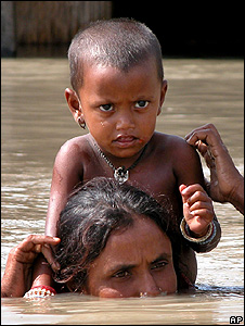 Young child being carried through floodwater (Image: AP)
