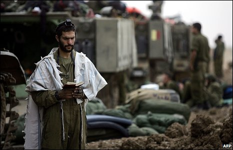 Israeli soldier prays near his tank
