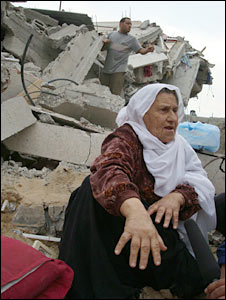 Fatima Minzaman sits next to her destroyed house