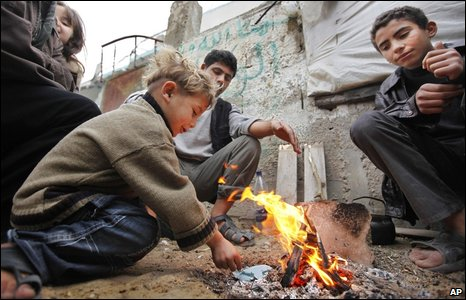 A Palestinian family huddle around a fire made with wood salvaged from destroyed houses, next to their destroyed house in the heavily hit area of Beit Lahiya.