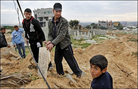 Palestinian boys sift through broken gravestones at a cemetery allegedly damaged by Israeli army bulldozers in Beit Lahiya (20/01/2009)