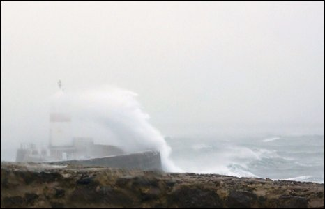 Strong winds blowing waves over a lighthouse.