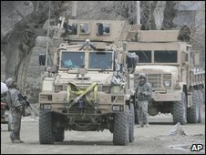 U.S. armored personal carrier vehicles are seen near the scene following a suicide car bomb attack in Chaparhar district of Ningarhar province, east of Kabul, Afghanistan on Saturday, Jan. 17, 2009