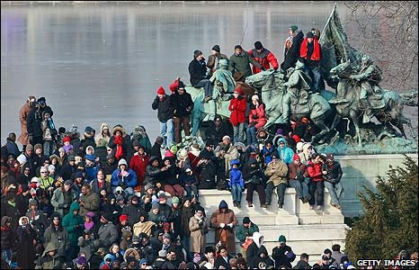 Crowds climb on a statue in the National Mall in Washington DC
