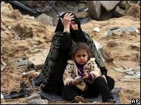 Madre e hija palestinas frente a escombros en Gaza