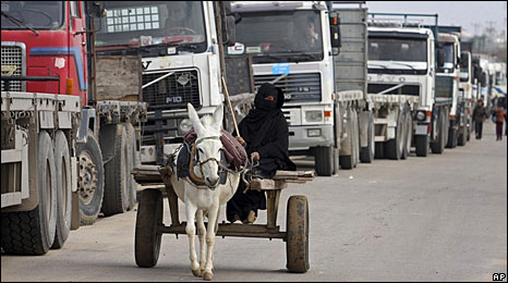 A woman rides past Palestinian trucks waiting on the border to load food in Rafah, in the southern Gaza Strip, 20 January 2009