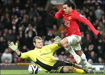Carlos Tevez is brought down by Roy Carroll