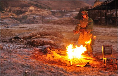 A soldier warms his hands by a fire