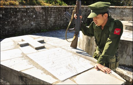 A soldier stands near a grave side