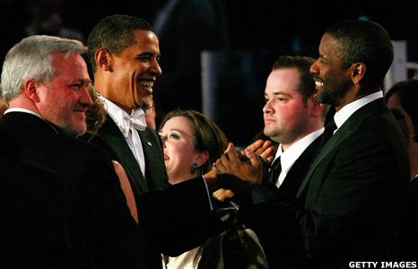Barack Obama greets Denzel Washington.