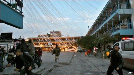 Palestinians run for cover during an Israeli strike over a UN school in Beit Lahia, 17/01