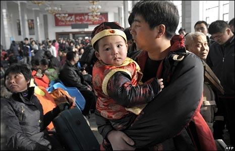 A boy dressed in Chinese traditional costume is held by his father as they wait for their train at Beijing Railway Station
