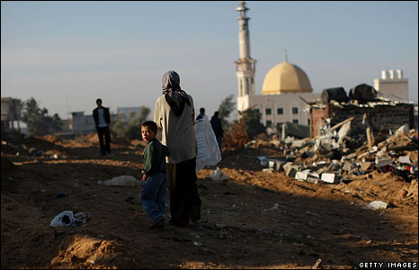 Two Gaza residents walk through rubble