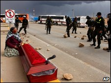 A woman sits next to a coffin containing the body of a demonstrator killed during clashes between the police and protesters in Patacamaya, Bolivia, in December 2008