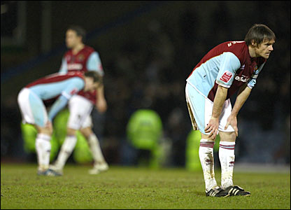 Burnley's Graham Alexander (right) epitomises the total dejection of the Championship side's players at the final whistle