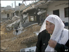 A Palestinian woman sits in front of her destroyed house in Gaza