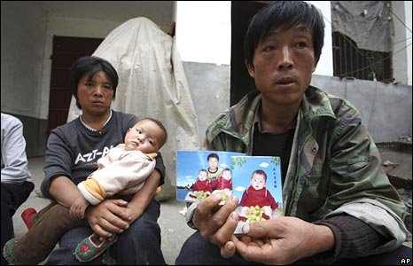 Li Xiaoquan holds up a photo of his twin daughters Li Xiaokai and Li Xiaoyan - who died of melamine poisoning - in Liti village, Henan province on 19 October 2008