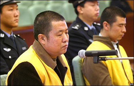 Geng Jinping, left, manager of a milk production base, and Geng Jinzhu, right, a driver at the base, stand trial at the Shijiazhuang Intermediate People's Court in Shijiazhuang, Hebei Province, on 30 December 2008