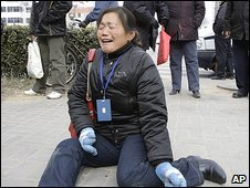Zheng Shuzhen, grandmother of a baby who died after drinking tainted milk, cries outside the Intermediate People's Court in Shijiazhuang, Hebei province, on Thursday
