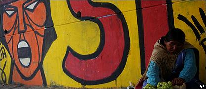 Una indígena vende frutas detrás de una pared que dice Sí