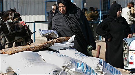 Palestinian woman looks at bags of food aid distributed by the Unrwa