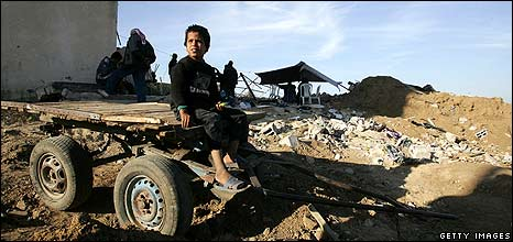 A Palestinian boy sits on a cart in front of his destroyed house in Gaza
