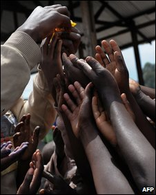 Displace people stretch for a handout at a camp in Kibati, Congo