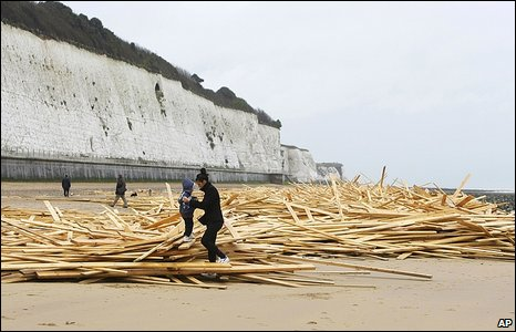 Woman and her son play on timber washed up on Ramsgate beach
