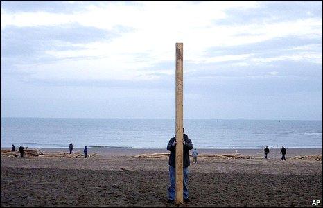 Man holding piece of timber on Ramsgate beach